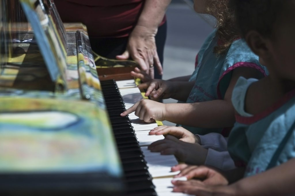 Les jeunes de l'installation Minime font une petite pause au piano en libre-service sur le parquet de la Maison de la Culture de Montréal-Nord