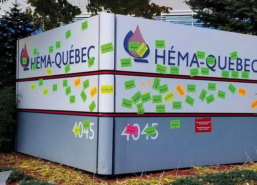 Pancarte d'Héma-Québec couverte d'autocollants CSN