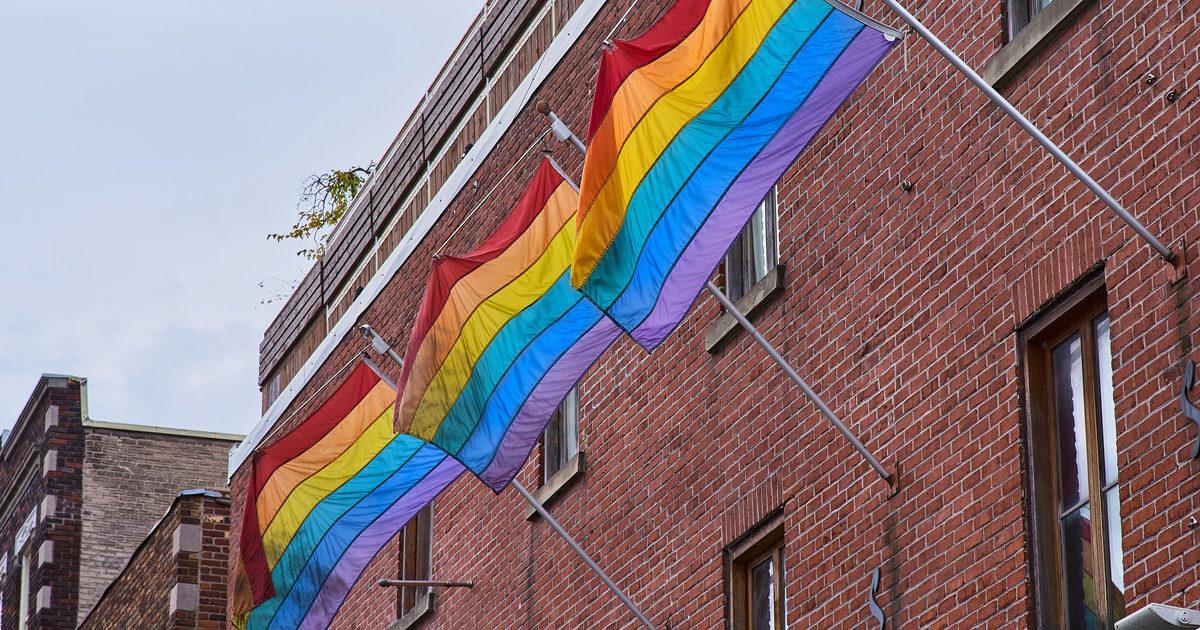 Trois drapeaux de la fierté accrochés à une édifice dans le quartier gai de Montréal.
