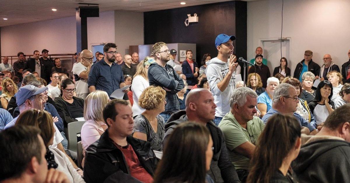 Photo de l'assemblée générale du STT de Barry Callebaut. Personne à casquette bleu au micro dans une grande foule.