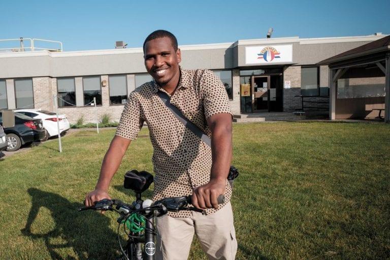 Image de Faram Hassan Doudoub, souriant avec son vélo devant l'usine Olymel