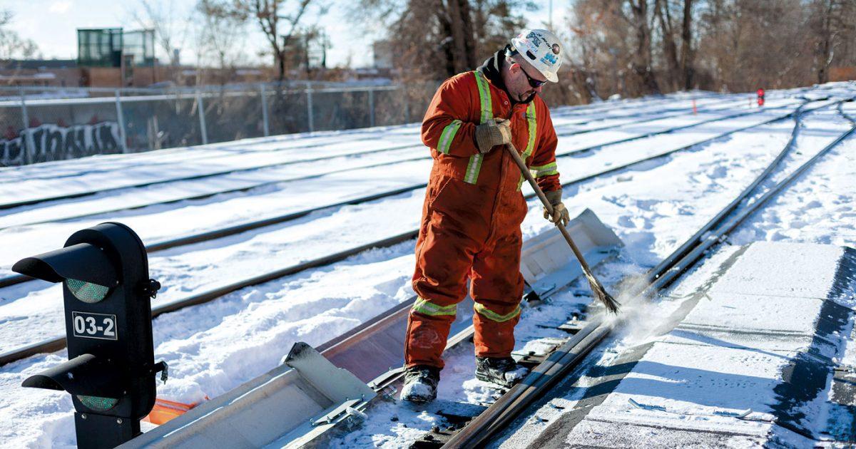 Travailleur de la construction nettoyant un chemin de fer l'hiver