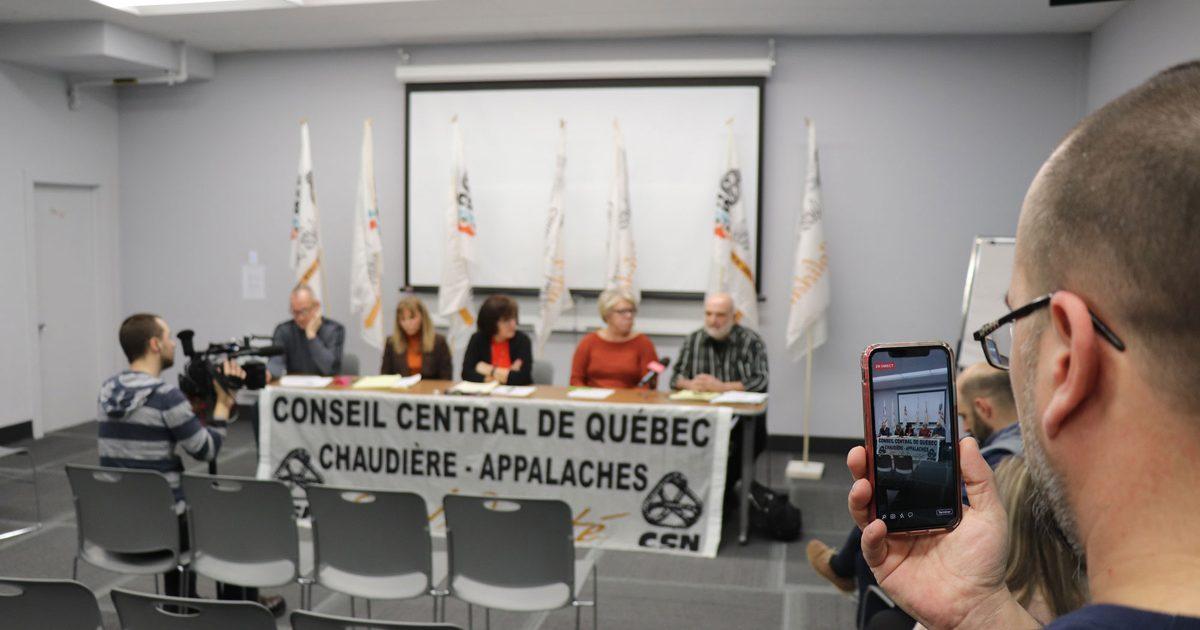 Photo de conférence de presse au CCQCA, 5 personnes à une table, une personne qui filme sur son cellulaire