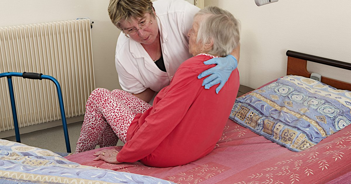 Care giver helping a senior woman   at home to go to bed