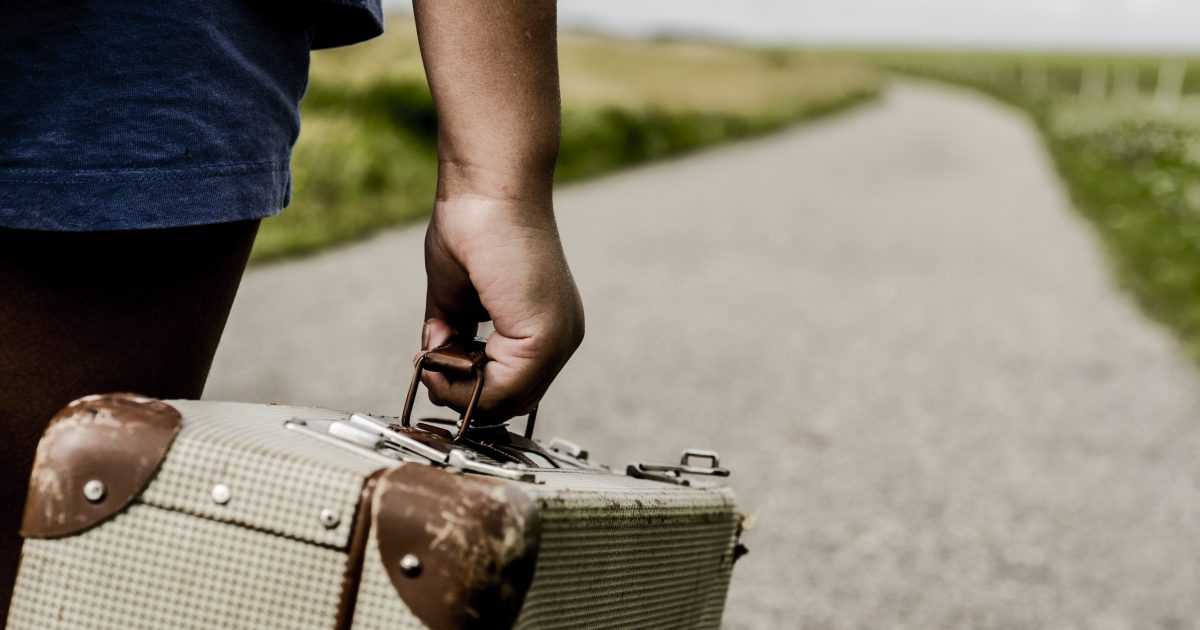 Refugee child goes on the road with her  suitcase