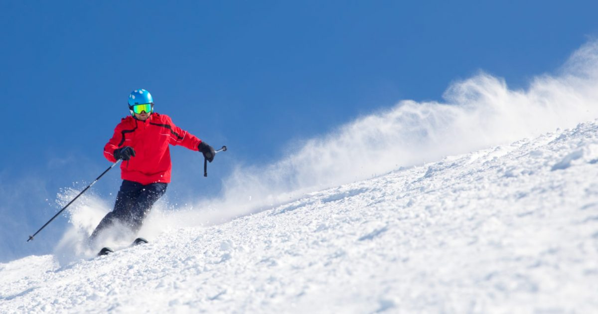 Man skiing on the prepared slope with fresh new powder snow.