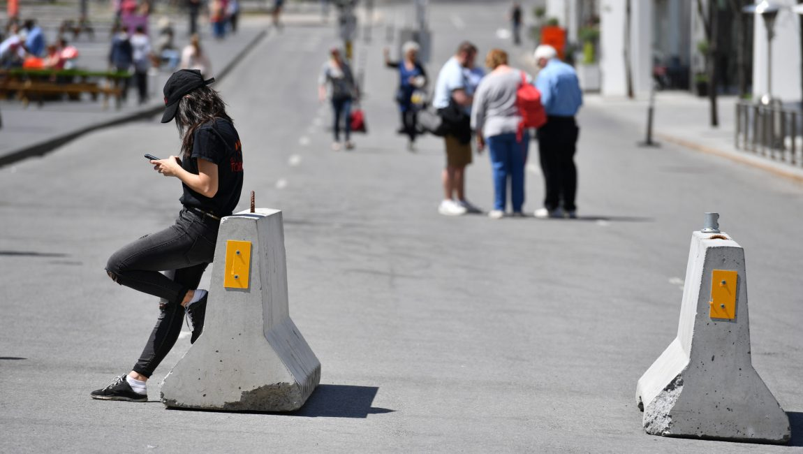 A young woman is looking at her smartphone on a warm and sunny day in Montreal-Canada