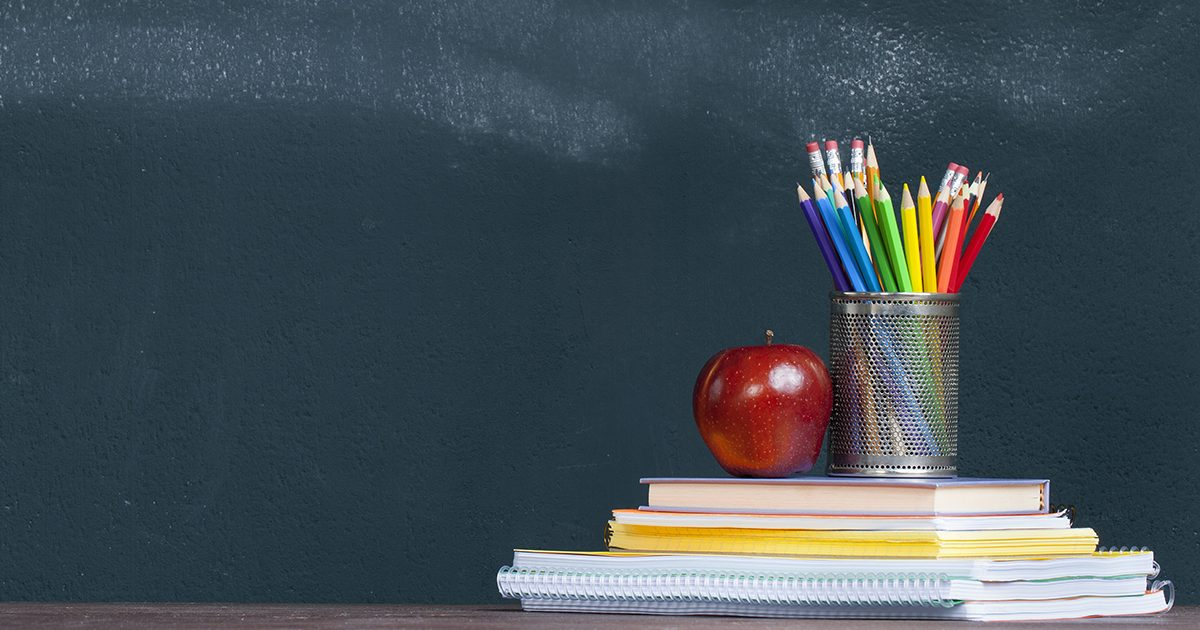 Pencil tray and an apple on notebooks on school teacher's desk.