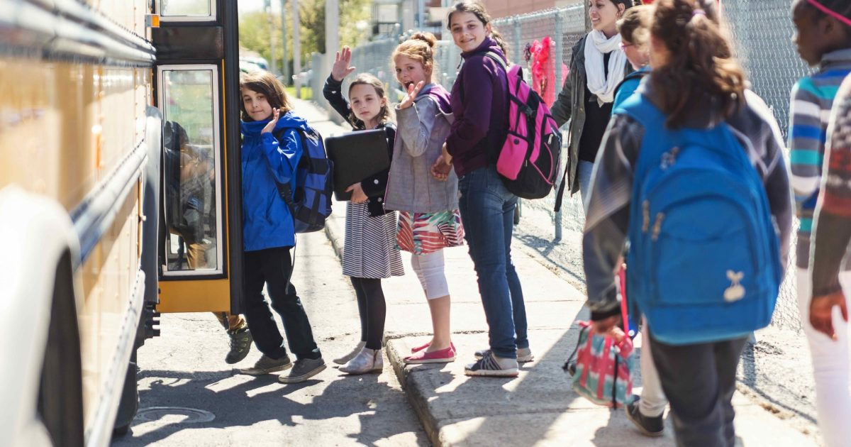 Kids in line waiting to get on school bus saying goodbye.